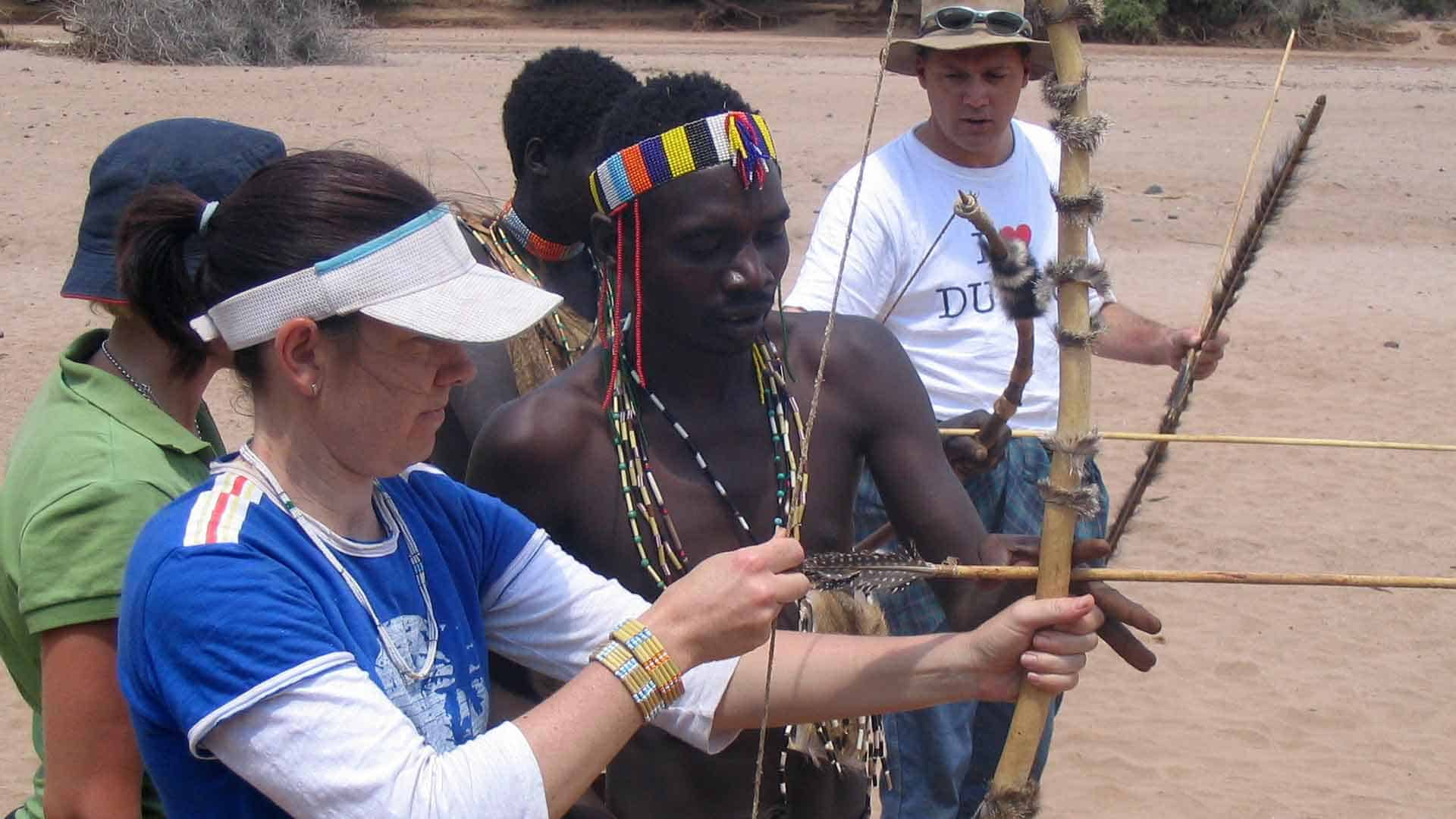 Girl learnig to shoot an arrow from members of the Hudzabe Tribe on an africa safari planning tour