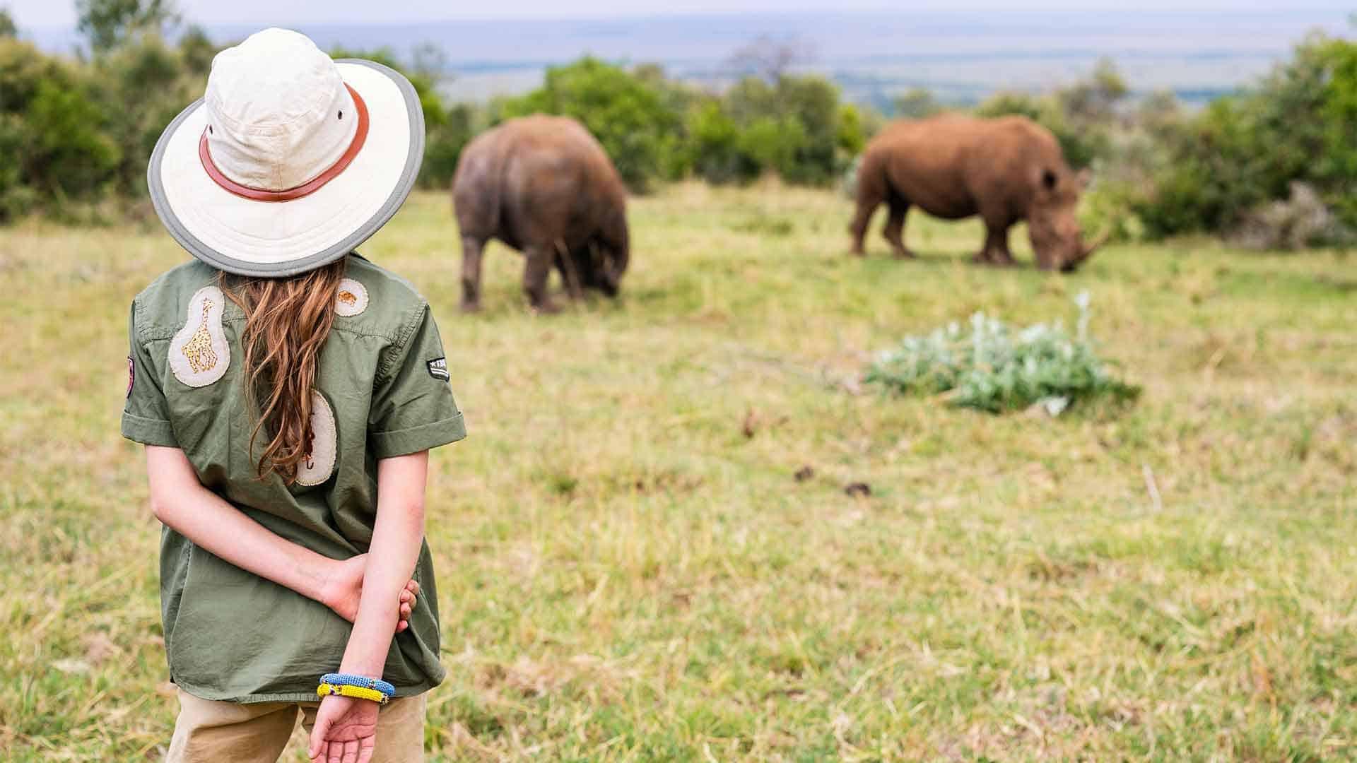 girl watching two Rhinos oin serengeti on safari tour to africa