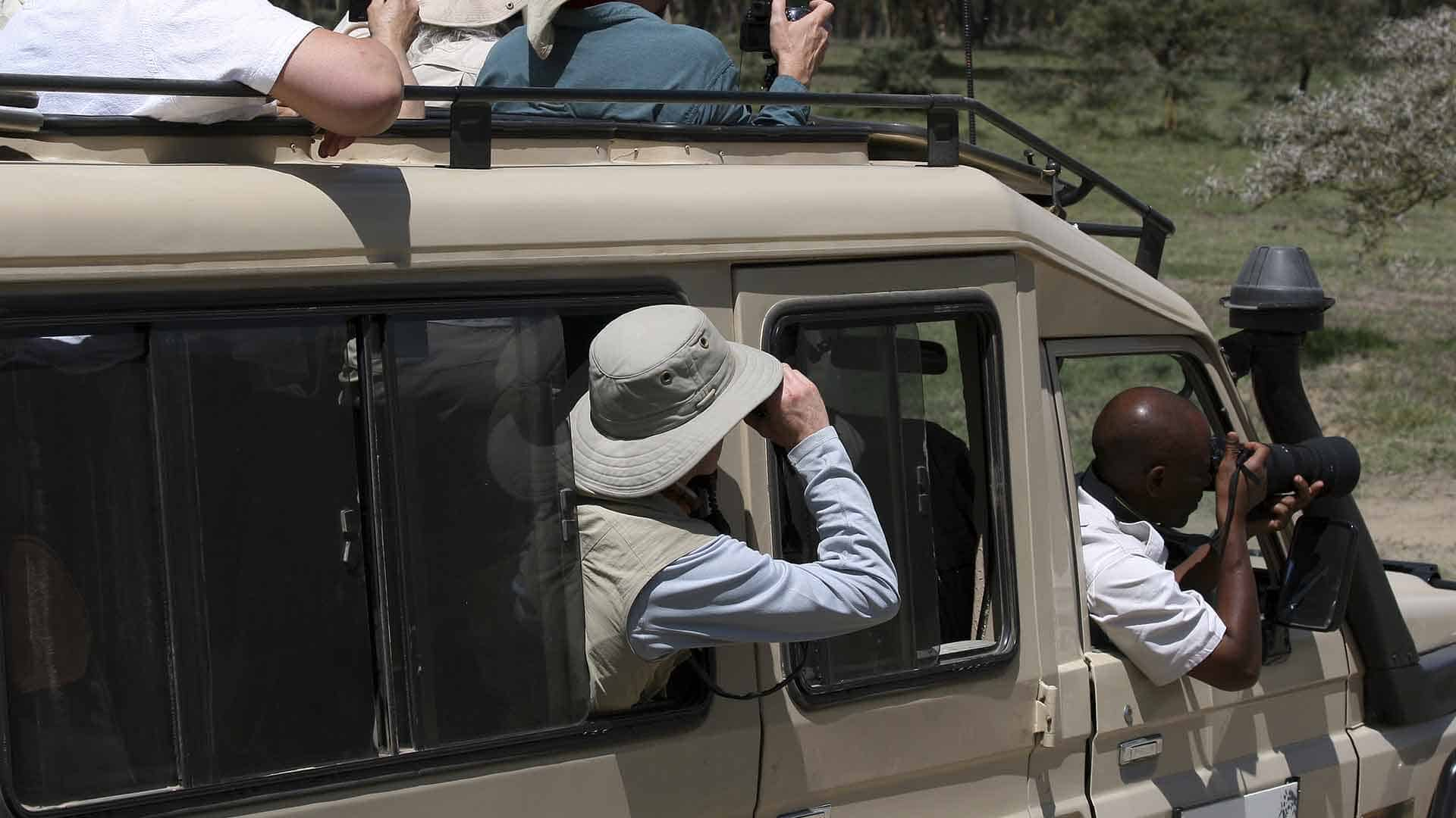 Tourists looking out from a safari vehicle on a safari tour to Serengeti